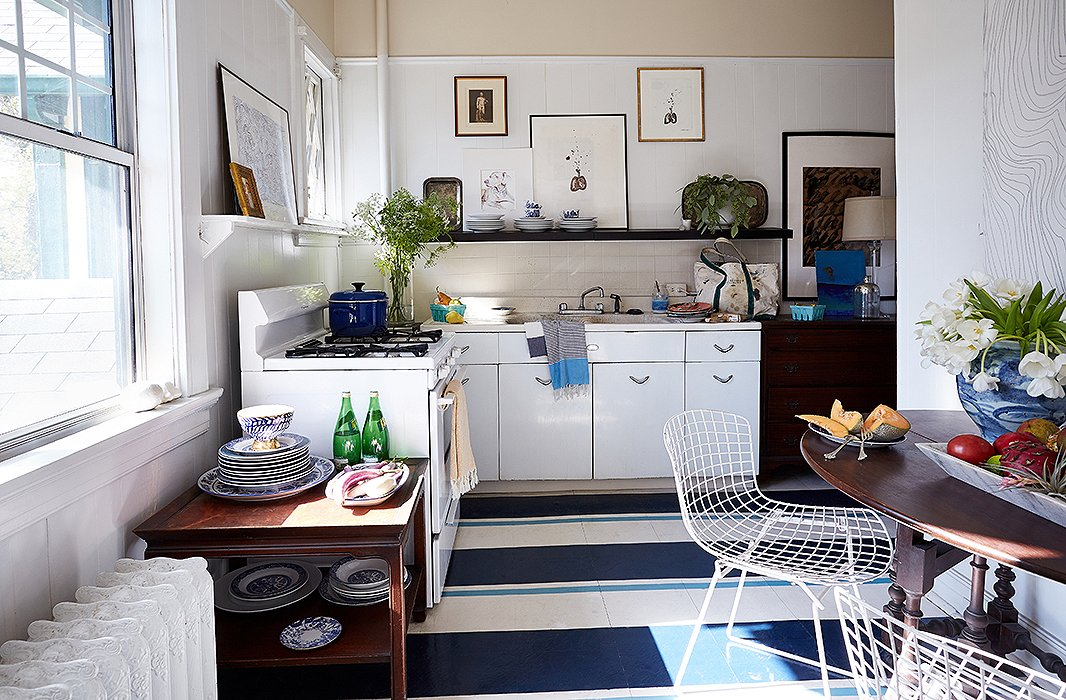 "The kitchen's linoleum floor received a bold makeover. ""Painting a floor is a way to add color, pattern, and interest in a space that normally doesn't have patterns or upholstery in it,"" William says. He kept the shelving open so that he could display his china and other collections."