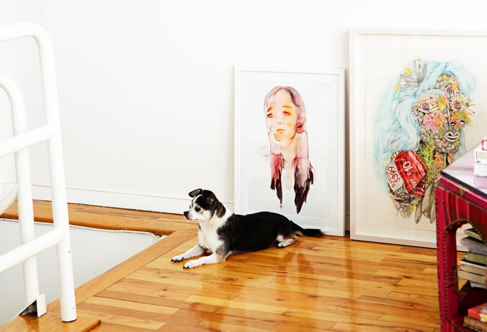 Oliver relaxes beneath a Kim McCarty watercolor. The art is leaned casually, leaving the rest of the wall clean and white.