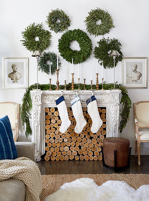The gallery wall goes green in this inventive look, which feels all the more charming thanks to a fireplace stacked to the brim with logs and hung with shibori-accented stockings. Photo by Tony Vu.
