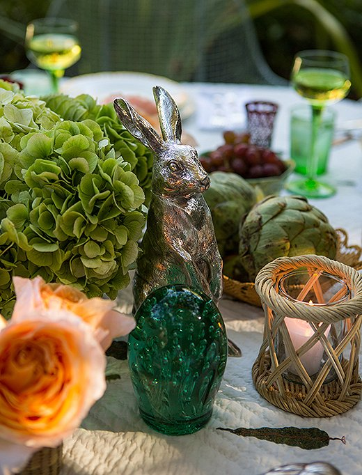 Soft candlelight gives everything a glow—including green glass globes that once graced Rebecca's parents' dining table in the Bahamas. The silver rabbits were a gift from her godfather.