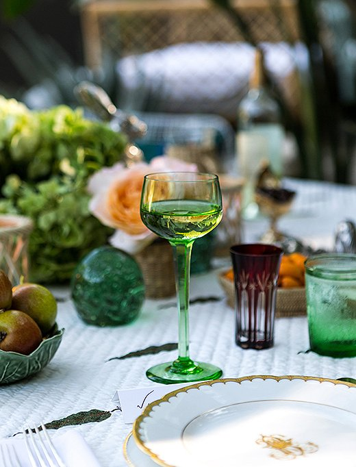 """I love nothing more than colored glasses,"" says Rebecca. Accented with deep-red juice glasses, the green goblets and tumblers play off the verdant surroundings."