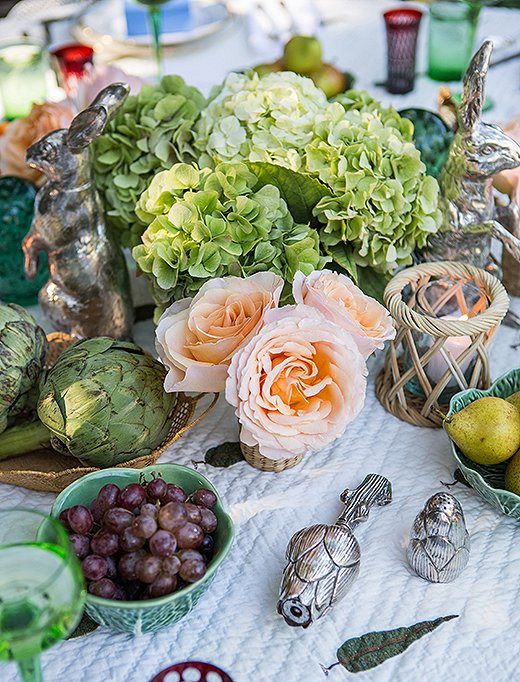 Bowls filled with artichokes, grapes, and pears add lush color and eye-catching shapes to the table.