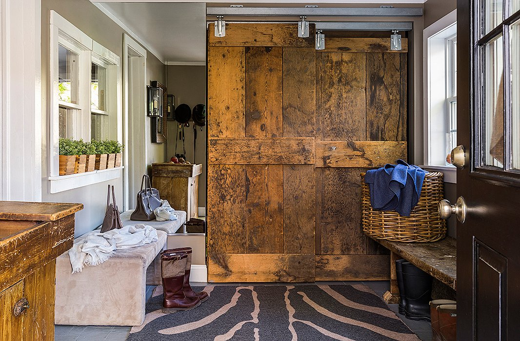 """With four kids you just have to be flexible and well organized, so we created this knowing that they're going to all come in with muddy boots,"" Alicia says of the mudroom, which is outfitted with a closet concealed by a custom-made barn door and bins for each member of the family. ""Is it always tidy? No, not always, but we try."""