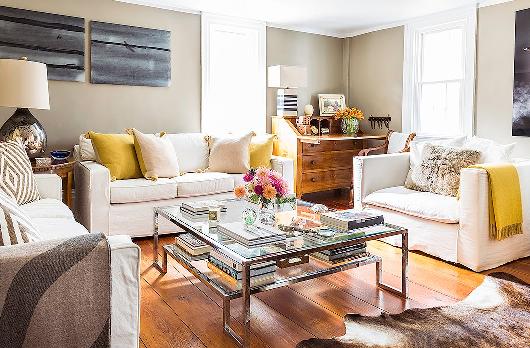 """The living room, which is used for entertaining and relaxing on the weekends, contains a mix of comfy seating, vintage pieces, and family heirlooms. """"The desk in the corner is an heirloom from Daniel's family,"""" Alicia explains. """"The white sofas worked well for that space They're not too deep, so they're not overwhelming."""""""