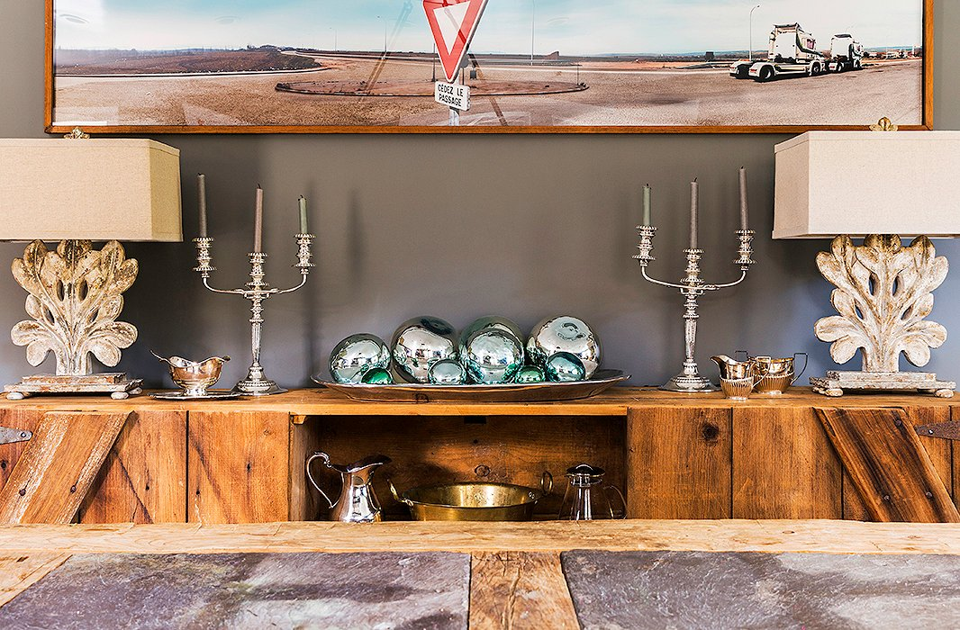 "A sideboard—also made of reclaimed barn wood—displays serving pieces and lamps that Alicia found on One Kings Lane. While weekday meals are served in the kitchen, the family moves into the dining room on the weekends. ""We'll lay out a nice breakfast for the kids and just hang out there."""