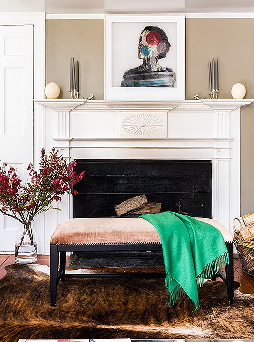 """We use the living room more in the fall and winter,"" Alicia says. ""We'll all sit on the floor by the fireplace and play a game."" One of her colorful throws is draped across a bench from One Kings Lane."