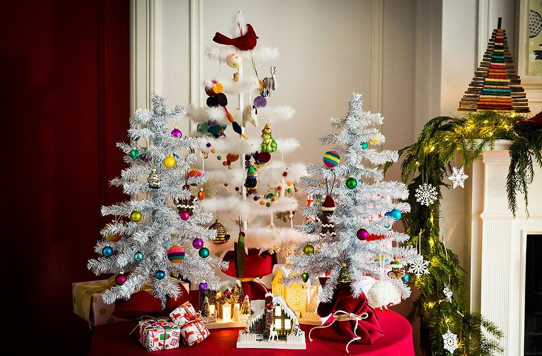 A trio of miniature trees can highlight a smaller collection of ornaments—think playful childhood favorites or baubles picked up on travels.