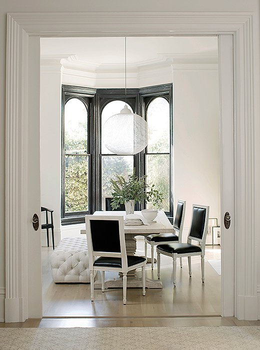 Black and white paint gives the home's traditional architecture a modern edge. Walls (flat) and trim (high gloss) in Benjamin Moore's White Wisp. Window frames in Benjamin Moore's Black, high gloss.