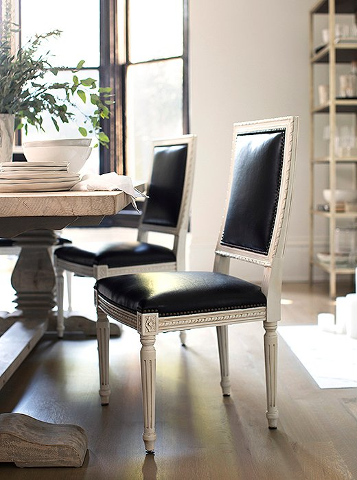 Black leather gives traditional Louis XVI-style chairs a glamorous update, while a weathered wood table brings the formality down a notch.