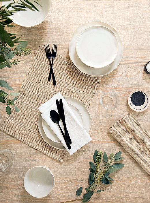 "Modern flatware contrasts with earthy ceramics on the table. ""I love that juxtaposition of really stark and modern and something with more of an organic edge,"" Erin says."