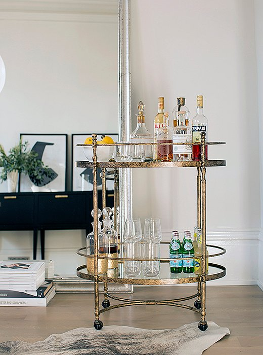 Leaned against the wall, an oversize silver mirror helps make the narrow room feel expansive—and plays off the metallic finish of the petite bar cart.