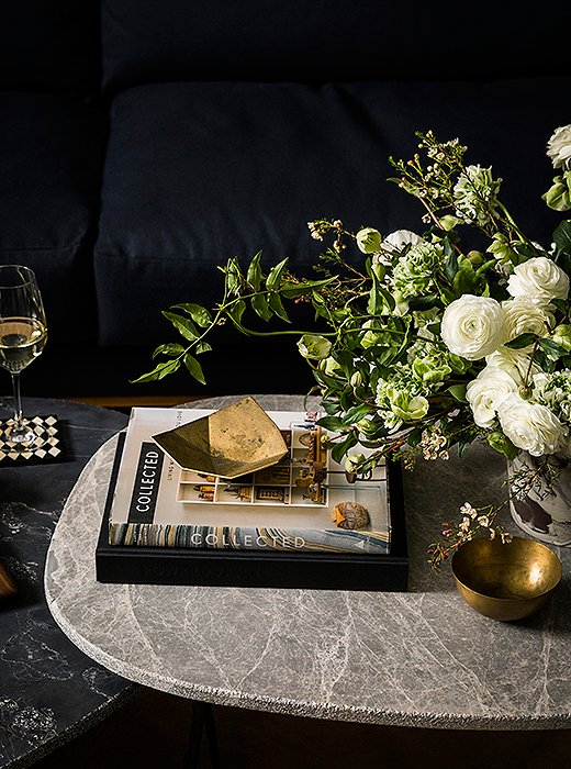 Marble coffee tables and brass accents make the space feel like a curated home.