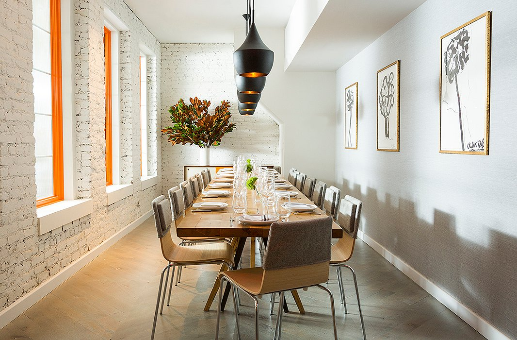 Dan chose to paint the window frames a bold orange to complement the Tom Dixon pendant lights and the Arthur Krakower prints, which he chose with the help of One Kings Lane Interior Design.