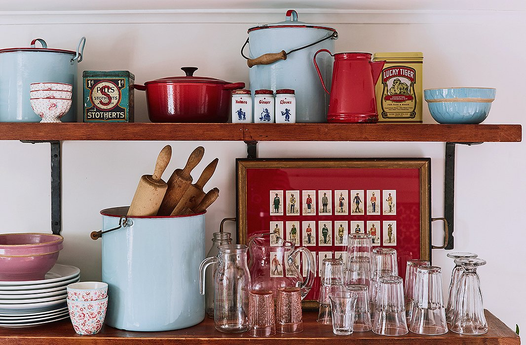 "Open shelving displays some favorite finds of Zanna and her husband, who's known simply as Rassi. Most are antiques picked up on their travels across the country. ""We're both quite little collectors of knickknacks,"" Zanna says. Vintage enamel cookware, antique tins, and a decorative tray make for a charmingly nostalgic vignette."