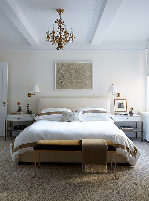 "Gilded details and warm metals add a bit of restrained opulence to the master bedroom. ""We didn't want the apartment to fall flat because we weren't using a lot of color,"" explains Vivian. ""The way we avoid that is in by playing with different textures. Metal is a great texture, although most people don't think of it as a texture."""