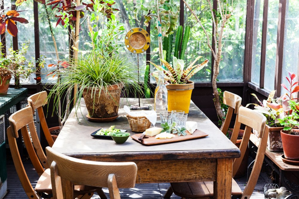 "A dining table doesn't need to be precious if it's in an outdoor environment. ""If you're at a garage sale and looking at an ugly table, paint it black, stick it outside, and let it age,"" says Stansfield."