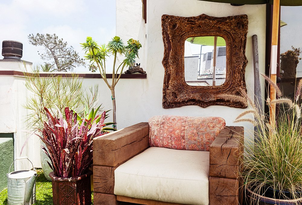 """""""You want to create intrigue with plants,"""" says Erin, who sourced for her rooftop garden one-of-a-kind pots andan unusual mix of flora that can sustain full sun. The carved wood mirror adds allure."""