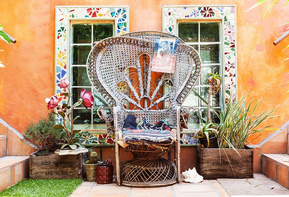 "Erin is a self-proclaimed garbage picker, and this peacock chair is one of her treasured finds. ""I carried this thing home,"" she boasts. A 1960s rose lamp lights the space at night. Even outdoors, the vibe is warm, comfy, and unfussy."