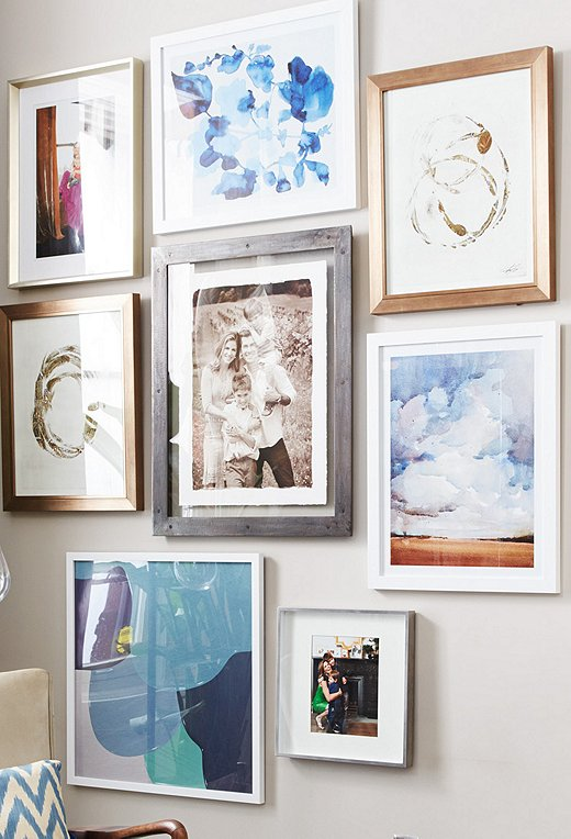 To warm up the spare wall, which featured only a large family portrait, we layered in a mix of paintings, photographs, and other artwork for a backdrop that instantly captivates in the entry.