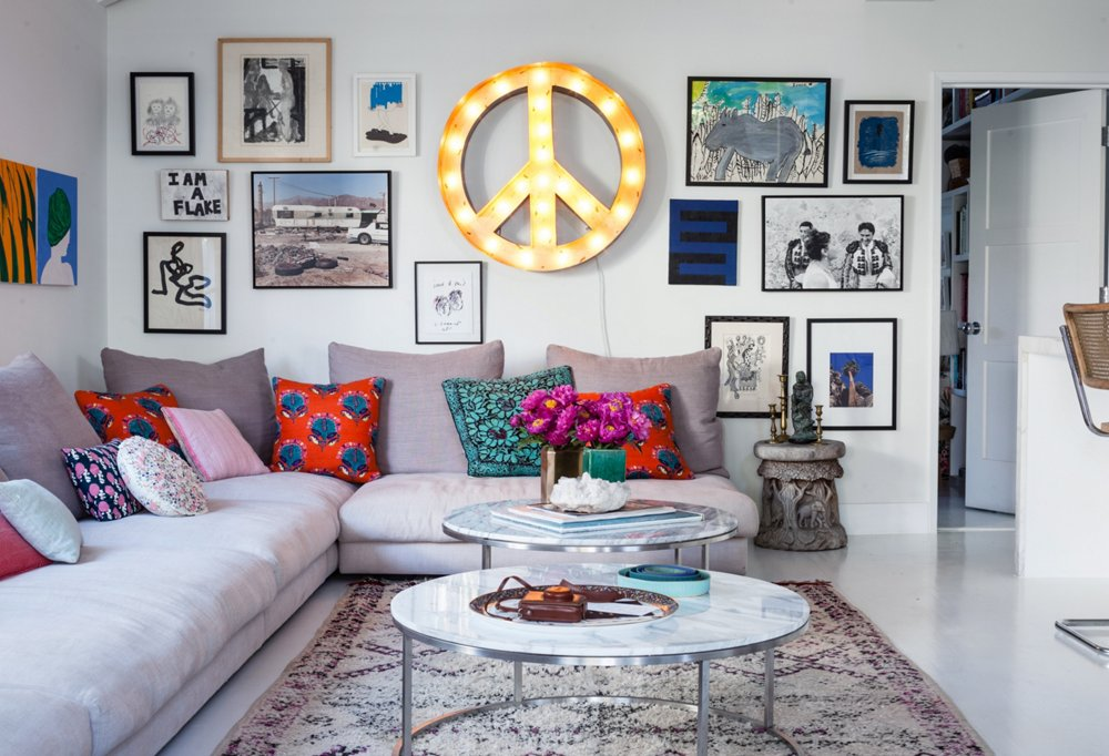 "A peace sign, found at Nickey Kehoe, lights up the living room day and night. On arranging art, Irene says, ""I really just throw art up on the walls. I build out from the center as I collect and just add new pieces."""