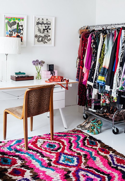 A cheetah-pattern chair and a colorful Moroccan rag rug are tempered by the simplicity of a white table and a Lucite lamp. Closet space is limited, so a rack holds the overflow in this corner space.
