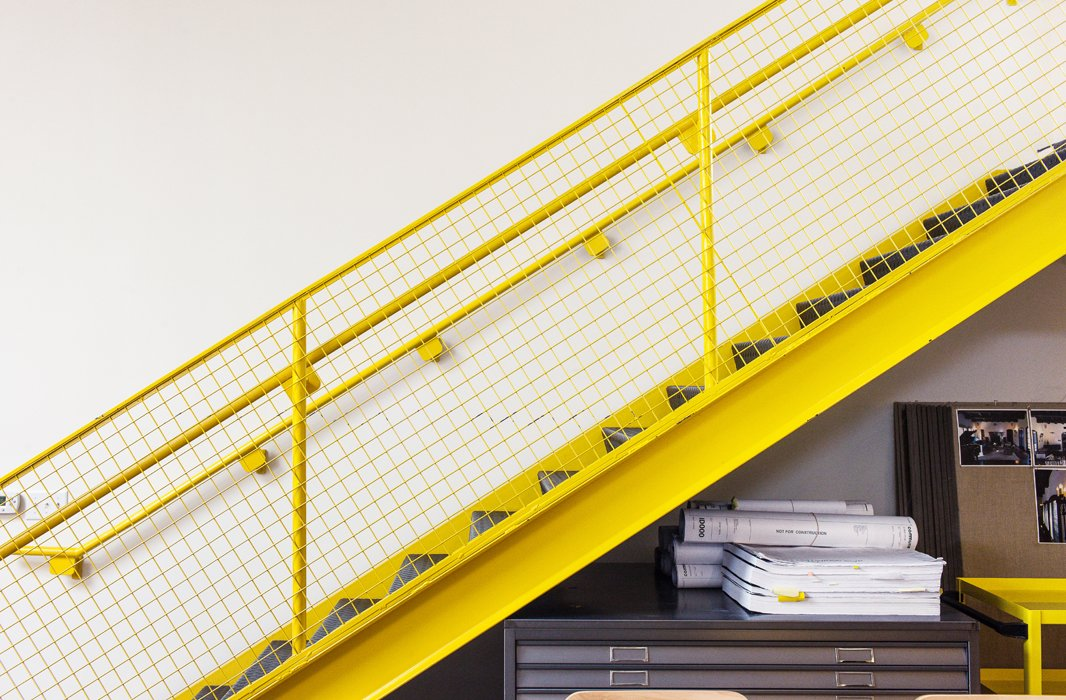 A bold hit of color in the nearly neutral office, the staircase was painted a mood-boosting shade of Safety Yellow.