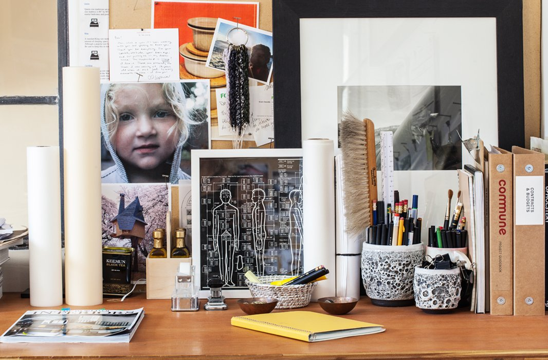 Bits and bobs, from family photos to handmade ceramics, dot Pam's desk.
