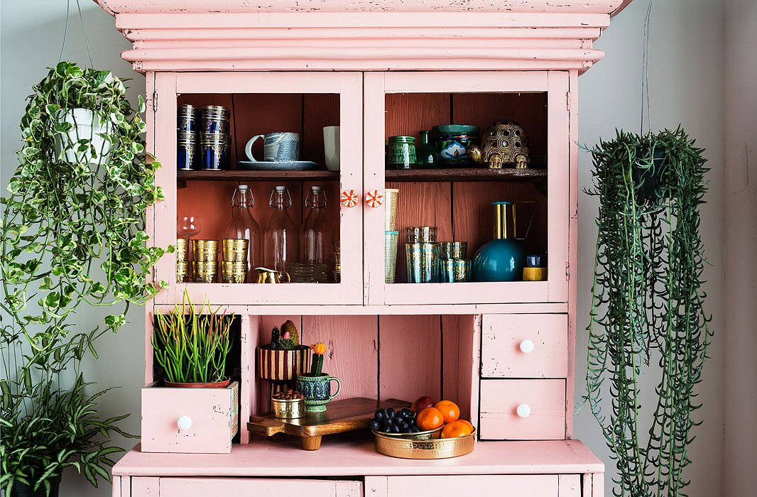 Justina bought the hutch for $100 off of Craigslist and painted it in Coral Flower by Glidden. One of the drawers was missing, so she decided to plant succulents in one of the remaining drawers to tie together the warm hues of the cabinet.