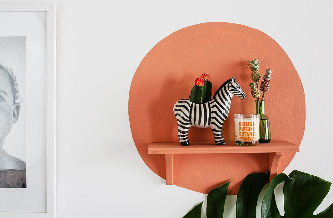 One of Justina's signature decorating moves, this painted shelf serves as a rotating vignette for small objects she loves. The zebra is a flea market find, and the tiny (live) pineapples are from the flower market.
