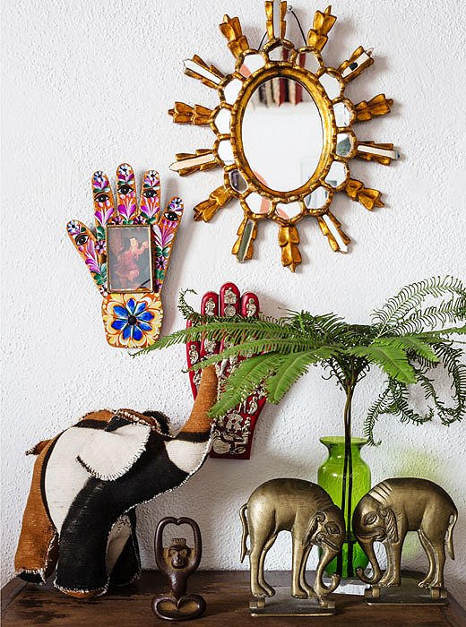 Kuba-cloth and Indian elephants stand guard beneath a Milagro hand and a Mexican punched-tin hand inset with a Botero print. The symbols of hands and eyes have always fascinated Justina.