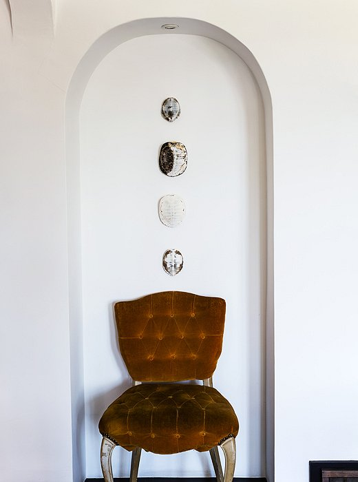 Making the most of every nook, Lizzie displays turtle shells and a vintage button-tufted chair in a small alcove.