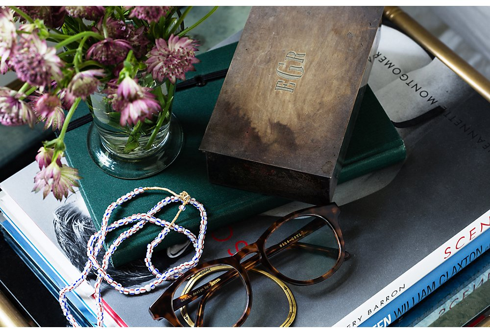 Lizzie suggests keeping a lidded box on the bedside table to store the odds and ends that can make the surface look messy. Here, her husband's glasses add a lived-in look.