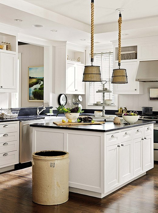 This kitchen uses an antique crock as a trash or compost receptacle.