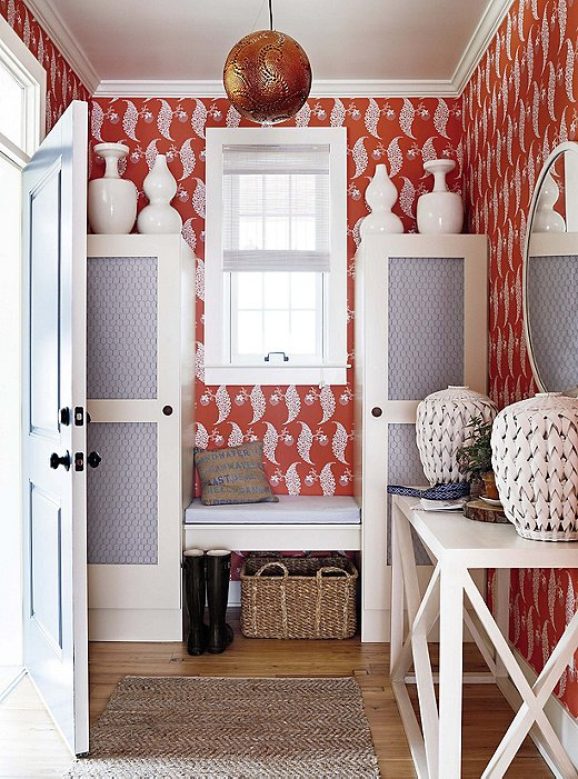 "In this ""wow moment"" entryway, the wallpaper, the woven baskets, the pendant light, and the pottery take the mind to the Orient, but it's all brought back home by pairing these elements with the cabinets lined with chicken wire."