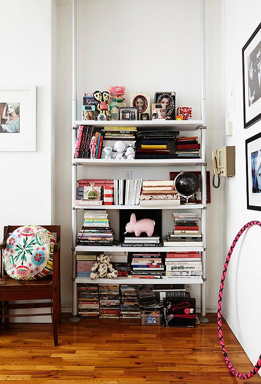 Ronson is drawn to kitschy little accents and anything and everything cute and girly. On this bookshelf in her living room, an evil-twin doll from her twin sister shares shelf space with the big-eyedBlythe doll she designed herself.