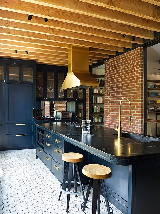 The dark kitchen, painted Farrow & Ball Black Blue, doesn't feel so dark with a wall of windows and a mirrored backsplash to reflect light around the space. The untreated wood beams introduce a more natural vibe.