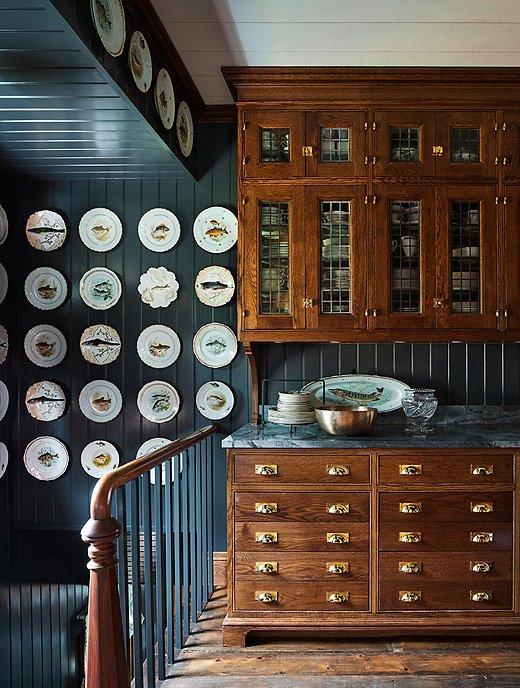 "One of Philip's favorite spaces in the house is the servery, attached to the dining room. Painted dark gray-blue and adorned with a collection of Limoges fish plates, the servery enables Philip and Mark to store the substantial collection of dishware they amassed and inherited over the years. ""It's the first house we've been in that has a space for all our serveware,"" Philip says."