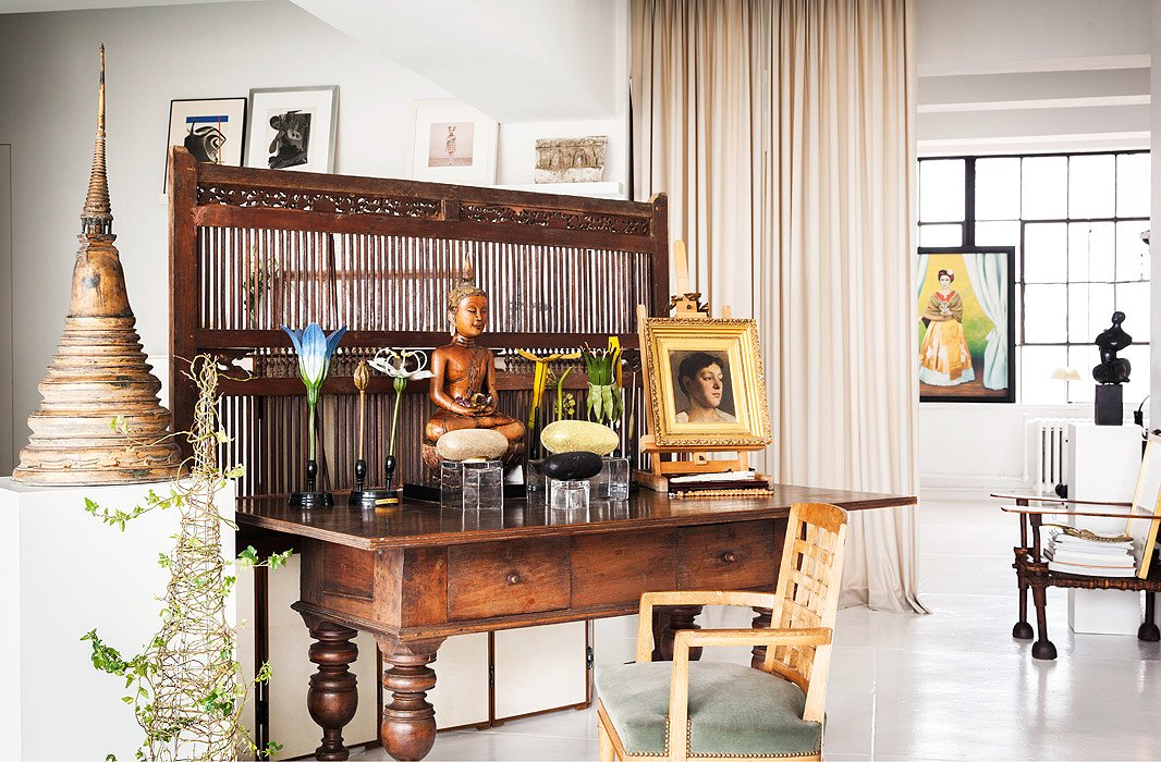 An Indonesian teak screen functions as a visual delineation between the entry and living areas. Once inside, visitors are greeted by ornamental flowers from Belgium and a Thai Buddha, both of which reside on top of an antique Dutch Colonial desk found in Sri Lanka.