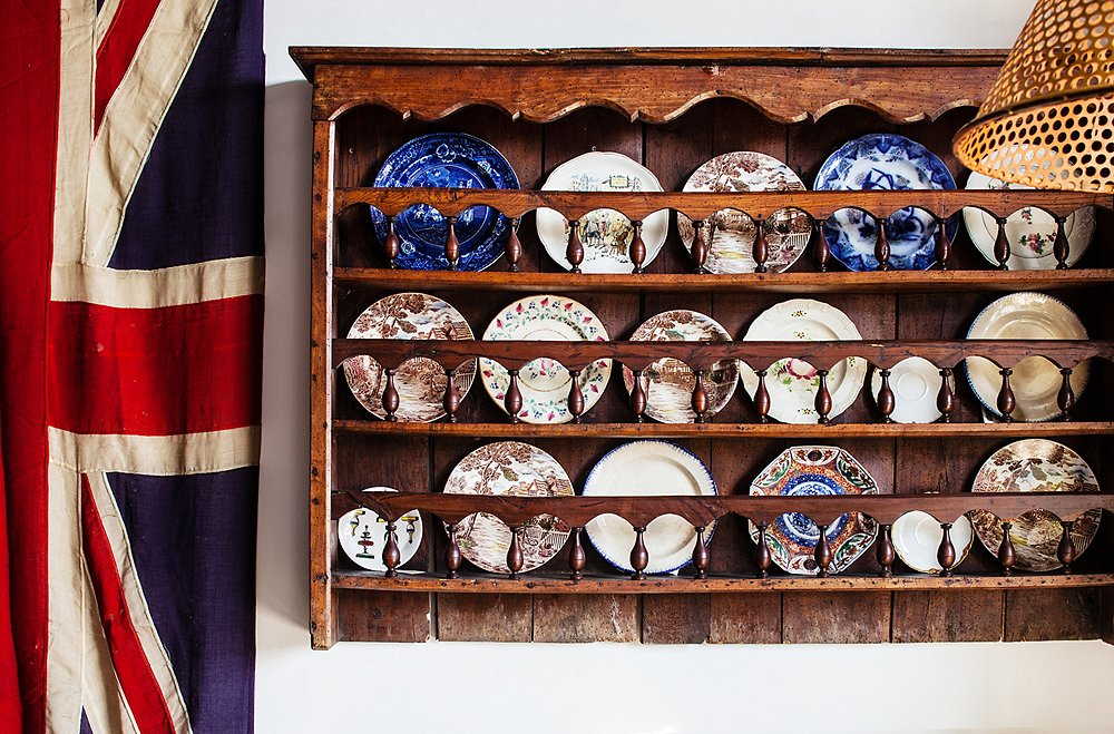"A 19th-century French plate rack demonstrates what the design duo do best in their store. ""The plates are vintage American, Japanese, and French, and we love them all mixed together,"" says Todd."