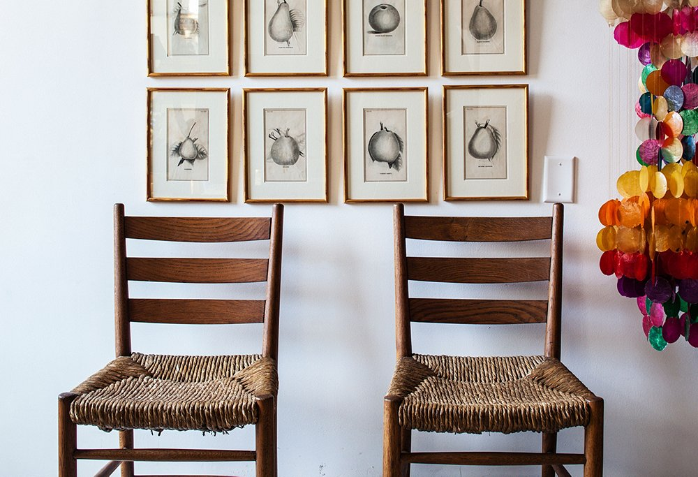 "Vintage Charlotte Perriand chairs, found at a Paris flea, accompany black-and-white etchings and a multihued capiz-shell pendant that the pair bought because they've ""never seen one like it, and we couldn't resist the colors,"" explains Todd."