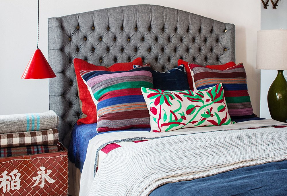 The bed (each tuft has a flat brass button) is from Amy and Todd's furniture collection, and it's topped with red vintage hemp pillows as well as striped pillows made from a vintage fabric they found and one that is covered in a red-and-green Oaxacan fabric.