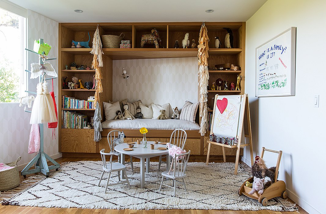 "The couple designed James's room with distinct ""components."" In addition to a sleeping area, they wanted a space for ""playing, reading, and being cozy,"" says Jessica. Jed built the table, which is encircled by mismatched chairs scored at flea markets. The ""set"" is unified with a light gray Farrow & Ball paint."