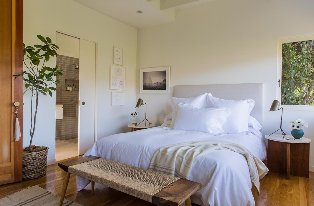 """Jessica wanted """"a little more ceiling height and lots of natural light"""" for the master bedroom, making it """"a refuge to relax in."""" A linen-covered headboard and whitebedding keep it airy. A custom bench by Mark Coppos and artwork by Russell Crotty and Sarah Anne Johnson add delicate pattern and texture."""