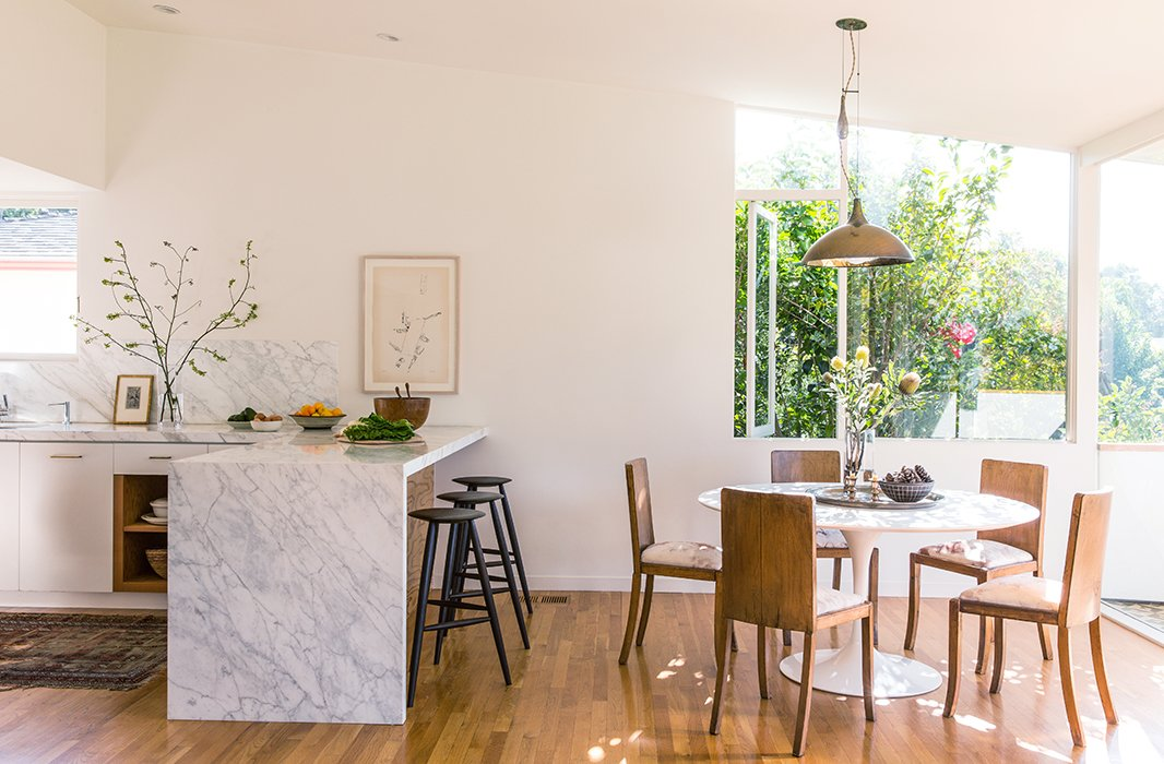 "The open dining area suits the couple's entertaining style. ""We like to serve family style so that people can make themselves at home,"" says Jessica. Stools from Sawkill Co. under a Carrara marble bar and a Michael Snow print make for a nice breakfast spot."