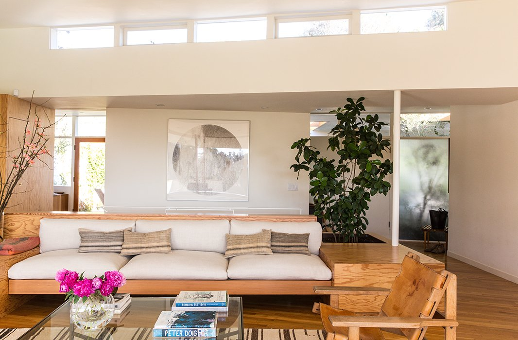 "The built-in sofa is the focus of the living room, accented with vintage-linen custom-made pillows. ""We like a mix of solids and patterns,"" says Jessica. ""And we're really drawn to washed linens and ethnic prints."" The large circular artwork is by Russell Crotty, a California artist and friend."