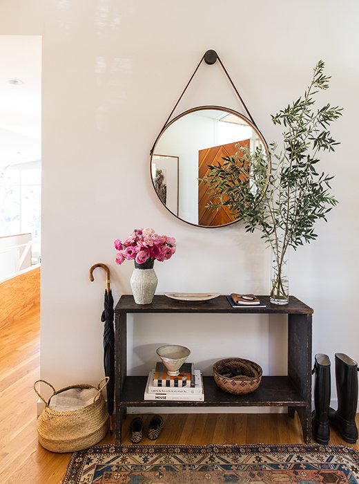 "The entry illustrates the couple's ethos of ""less is more."" A console from Galerie Half holds pottery from Californian and Japanese ceramists. (David Korty and Akio Nukaga are favorites.) The front door, designed by Jed, is seen in the BDDW mirror's reflection."