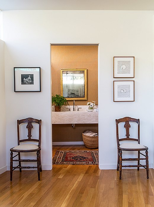 "The powder room pairs ""traditional with modern pieces""—a mix the couple enjoys. ""It makes it cozier and more comfortable,"" says Jessica. Jed's mother gifted the chairs (upholstered in Libeco linen)."