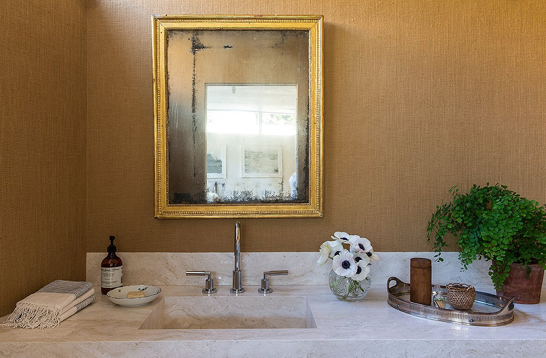 A cool travertine vanity is a perfect foil to the 19th-century mirror. The color throughout the home is Benjamin Moore's White Dove, but for this space, Jessica chose burlap wallpaper. Anemones and maidenhair ferns are two of the couple's favorite plants.