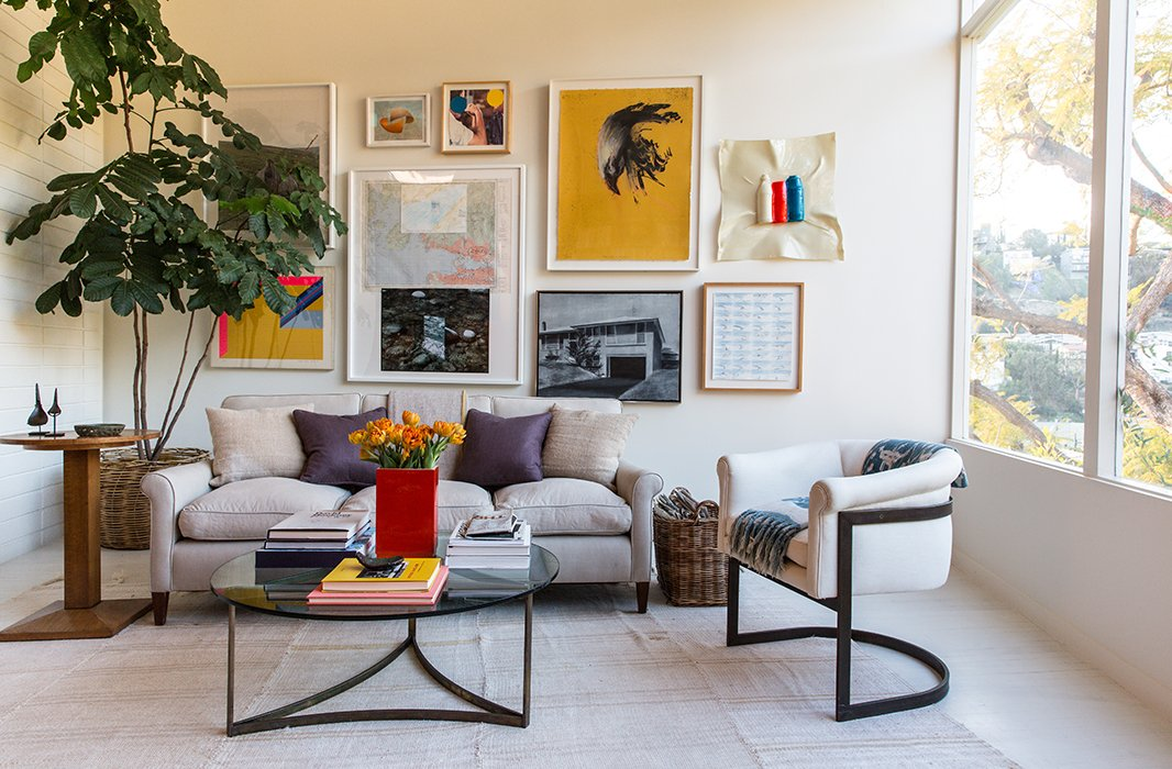 """Jed's parents and the couple are passionate art collectors, resulting in a bold gallery wall. The piece """"hiding behind the tree is one of Jed's,"""" says Jessica. The furniture is a mixof """"custom, vintage, flea market, and inherited pieces, like a Milo Baughman chair."""""""