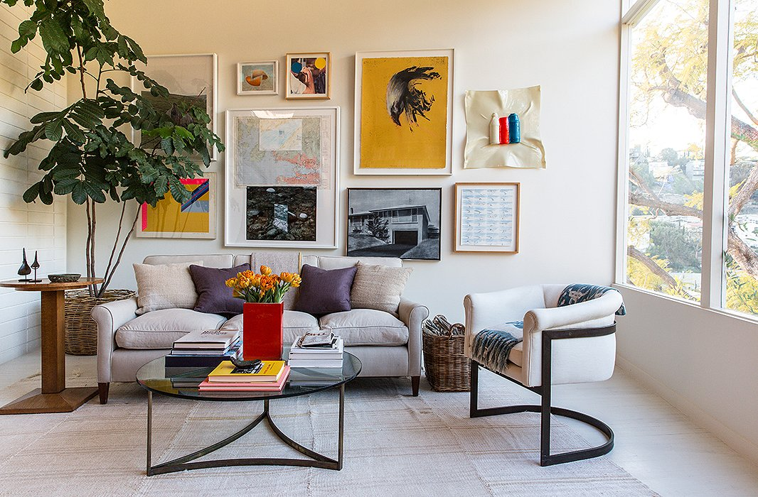 "Jed's parents and the couple are passionate art collectors, resulting in a bold gallery wall. The piece ""hiding behind the tree is one of Jed's,"" says Jessica. The furniture is a mix of ""custom, vintage, flea market, and inherited pieces, like a Milo Baughman chair."""